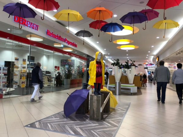 Visual Merchandising in Shopping Center mit Regenschirmen